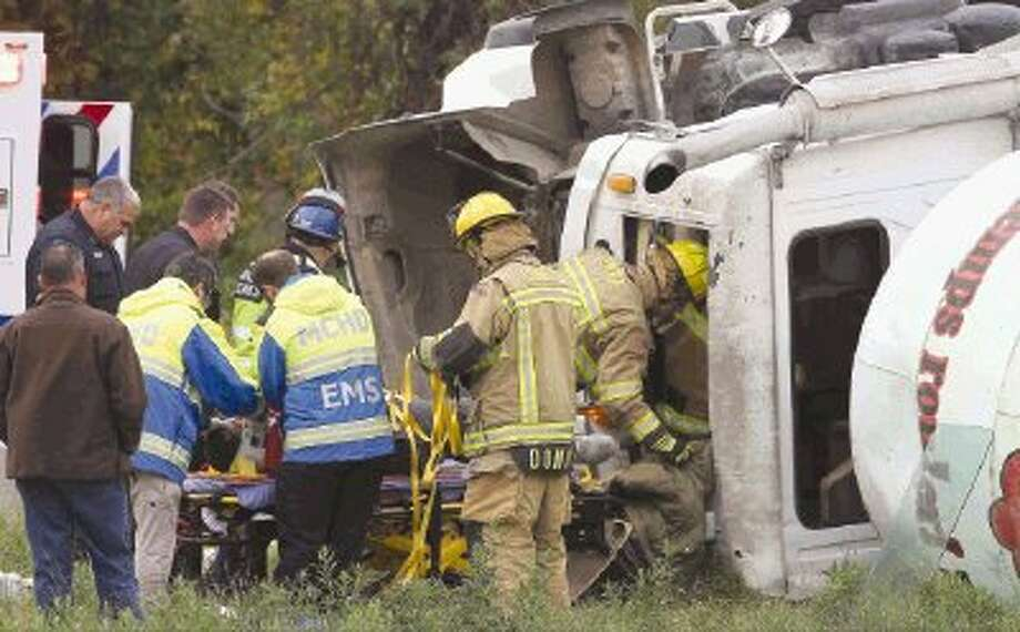 Conroe firefighters and Montgomery County paramedics work to free a man from an overturned cement truck on F.M. 1488 near I-45 South Thursday morning. Photo: Staff Photo By Jason Fochtman / Conroe Courier