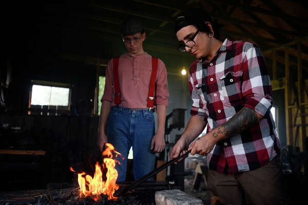 Joe Dannar, left, watches as Chase Lehman pulls his hot railroad spike from the fire during a bladesmithing class at the Spindletop-Gladys City Boomtown Museum on Saturday.  Photo taken Saturday 9/24/16 Ryan Pelham/The Enterprise