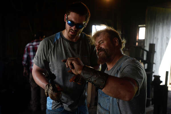 Tommy Gillespie gets help from blacksmith Rob Flurry during a bladesmithing class at the Spindletop-Gladys City Boomtown Museum on Saturday.  Photo taken Saturday 9/24/16 Ryan Pelham/The Enterprise