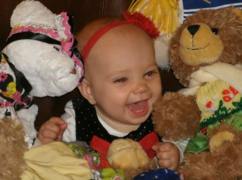 Nine-month-old Kate Koury, daughter of Ginna and Kevin Koury, enjoys being surrounded by dolls and bears at the annual Salvation Army Christmas Silver Tea Sunday at a private home in north Conroe.