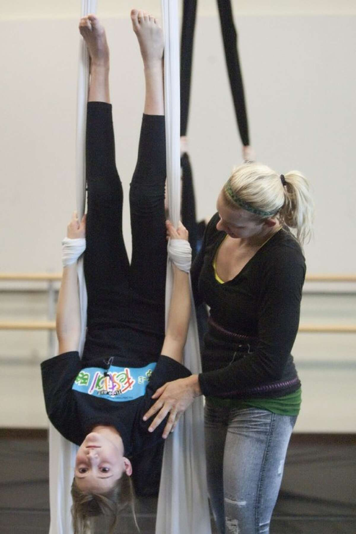 Jill Crook demonstrates silk aerial techniques to Carina Masuelli Friday at the John Cooper School.