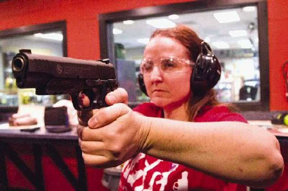 Paula Gamber, a concealed handgun licensing instructor, demonstrates shooting snap caps during a class Tuesday night at Shooter's Station for A Girl and A Gun Club Cut and Shoot/Conroe chapter. The goal of the organization is to teach women how to shoot properly, build confidence while shooting and to have fun at the same time. Photo: Staff Photo By Ana Ramirez / The Conroe Courier