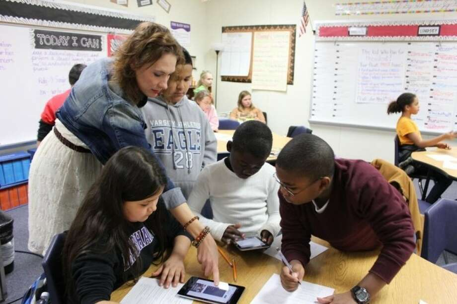 Dana Schultz, a fifth-grade teacher at Parmley Elementary, shows her students how to research information on the Internet using a school tablet.
