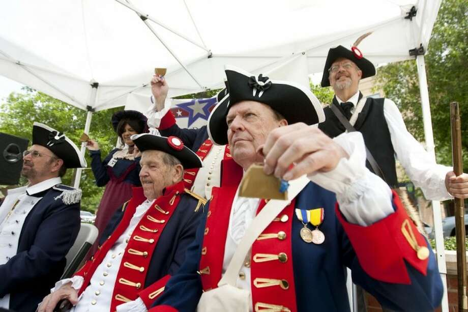 Members of the Lone Star Chapter of The Sons of the Republic and the Thomas Bay Chapter of the U.S. Daughters of 1812 ring bells to celebrate the bicentennial of the War of 1812 on Market Street in The Woodlands on Monday.