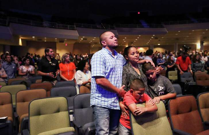 Victor Rivas worships with his wife, Iliana Larin, and sons Victor, front center, and Anthony during a Spanish-language service at Champion Forest Baptist Church, which has greatly increased its Latino membership.