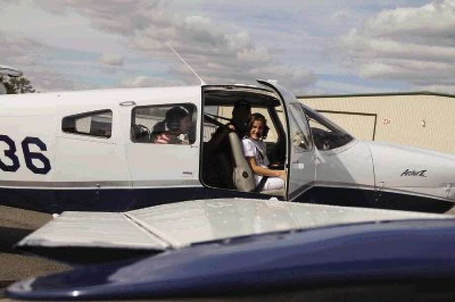 Aliyah Khan, 14, enjoys her flight time during the Challenge Air event for special-needs children at Lone Star Executive Airport in Conroe Saturday. More than 130 children had the opportunity to ride in a plane, as well as pilot it, thanks to numerous volunteers and area pilots. / James Ridgway, Jr.