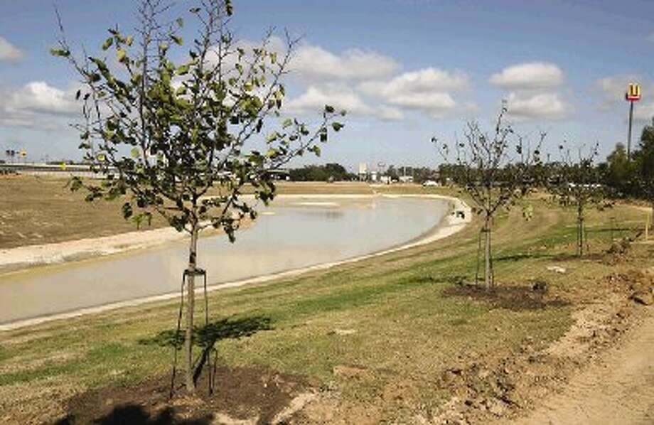 Redbud trees line one of two amenity ponds built at the southeast corner of Interstate 45 and Texas 105. The redbuds are among several species - 58 trees in all - that are being planted this week.