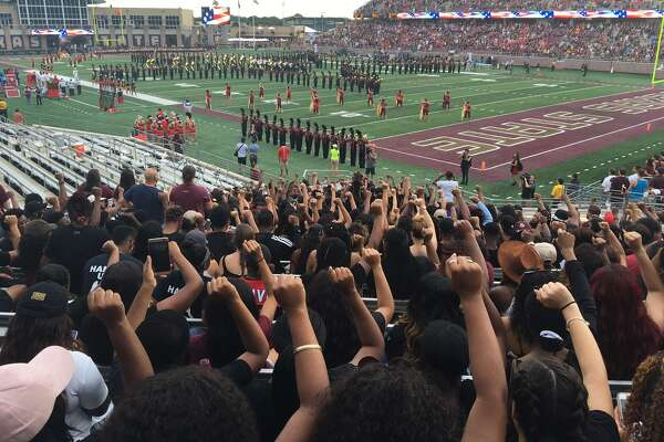 A group of Texas State students raise their fists while sitting during the national anthem before a college football game between No. 6 University of Houston and Texas State at Bobcat Stadium in San Marcos on Saturday, Sept. 24, 2016.