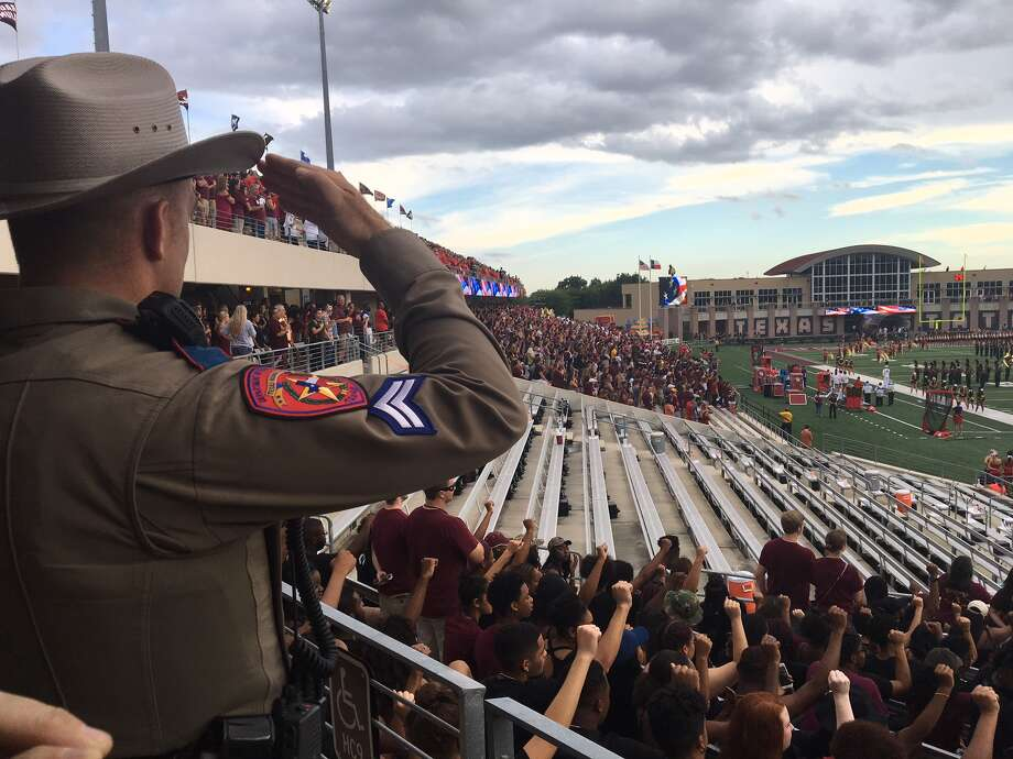 A group of Texas State students raise their fists while sitting during the national anthem before a college football game between No. 6 University of Houston and Texas State at Bobcat Stadium in San Marcos on Saturday, Sept. 24, 2016. Photo: Joseph Duarte