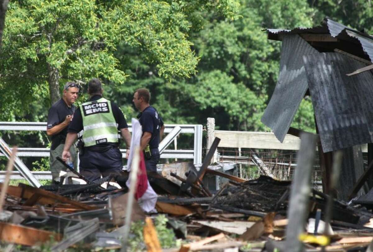 Officials examine the scene of a home explosion Tuesday in Dobbin. Two adults and a child were transported from the home by medical helicopter. The cause of the explosion is still under investigation.