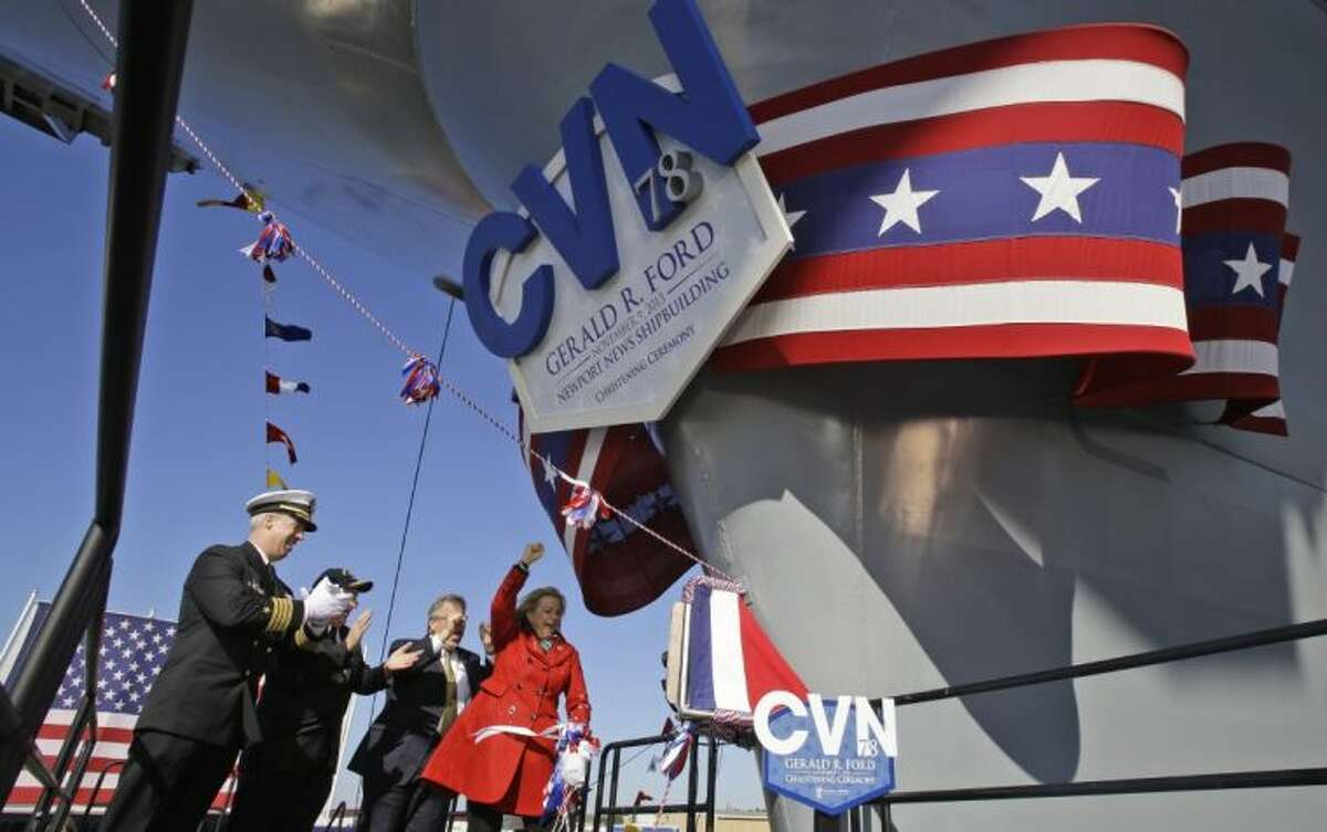 Susan Ford Bales, daughter of former President Gerald R. Ford, right, cheers after christening the Navy's newest nuclear powered aircraft carrier USS Gerald R. Ford at Newport News Shipbuilding in Newport News, Va., Saturday.
