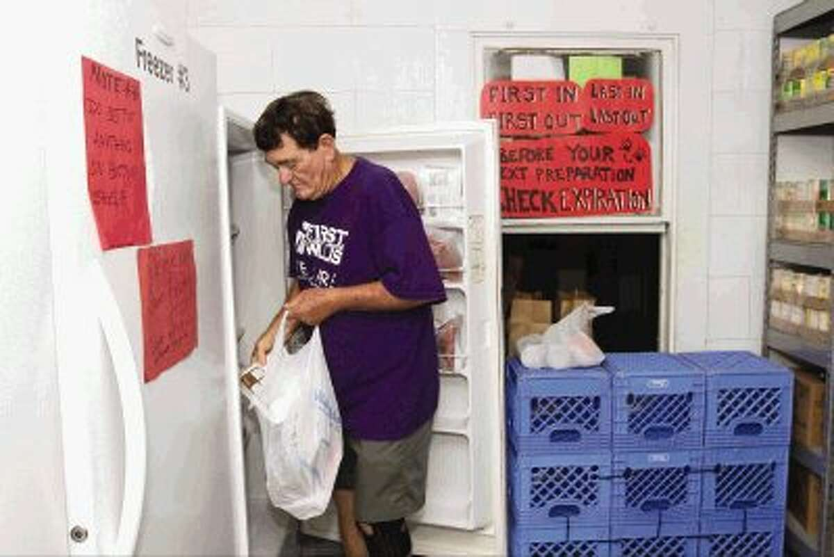Richard Sykes takes groceries out of a freezer at the TLC Food Pantry in Willis Thursday. Volunteers at the pantry are asking for donations to help feed out-of- school children who have working parents.