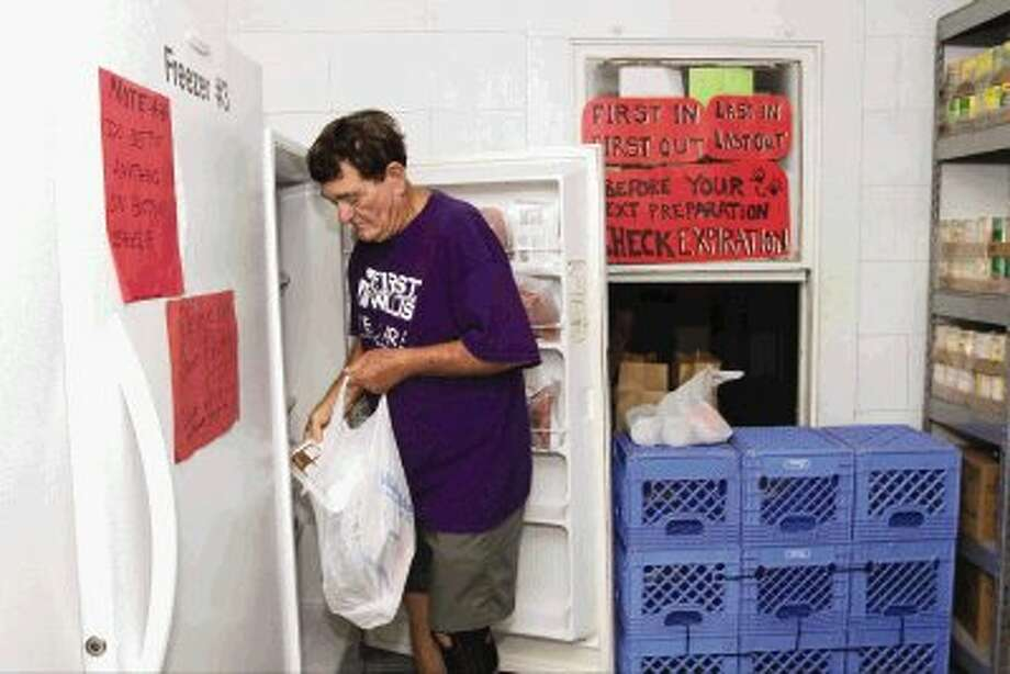 Richard Sykes takes groceries out of a freezer at the TLC Food Pantry in Willis Thursday. Volunteers at the pantry are asking for donations to help feed out-of- school children who have working parents. Photo: Staff Photo By Jason Fochtman