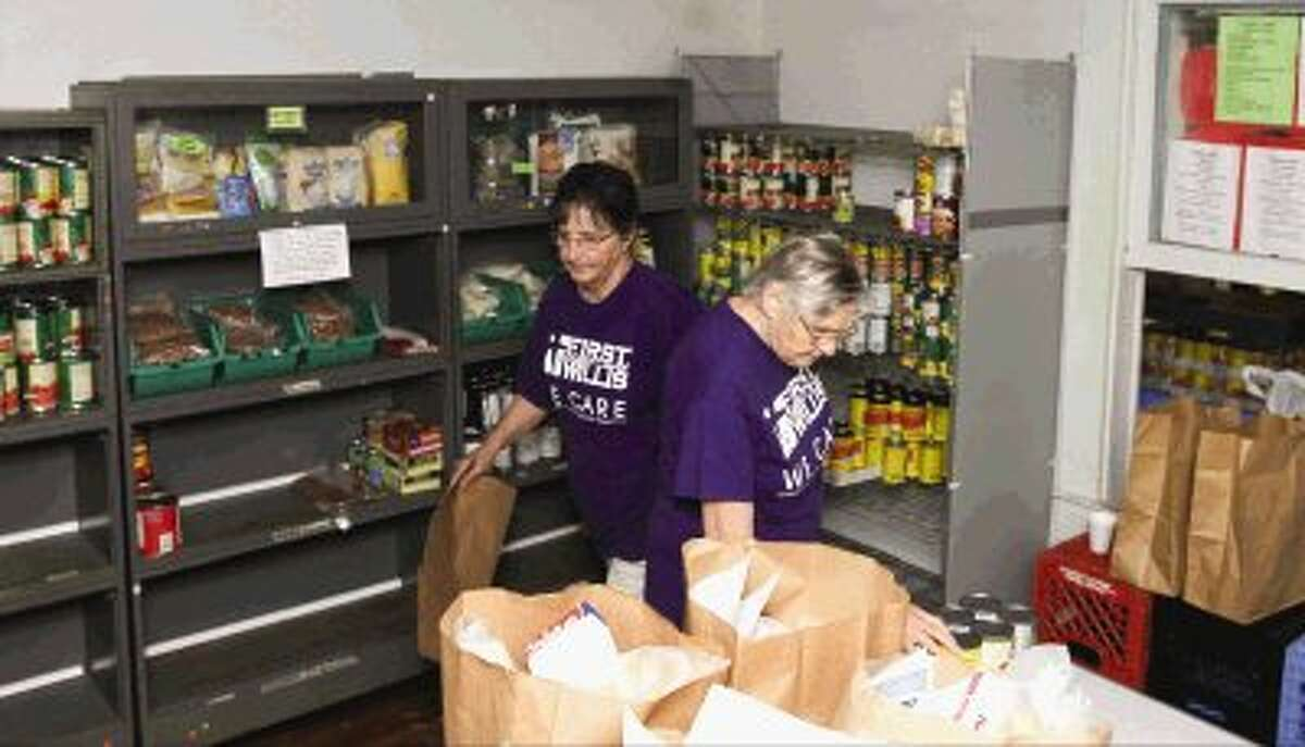 Volunteers with the First Baptist Church in Willis assemble bags of food at the TLC Food Pantry in Willis Thursday.