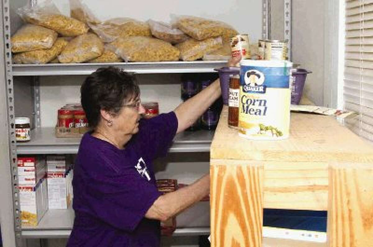 Clara Anderson, a volunteer with the First Baptist Church in Willis, assembles bags of food at the TLC Food Pantry in Willis Thursday. The pantry is asking for donations to help feed out-of-school children who have working parents.