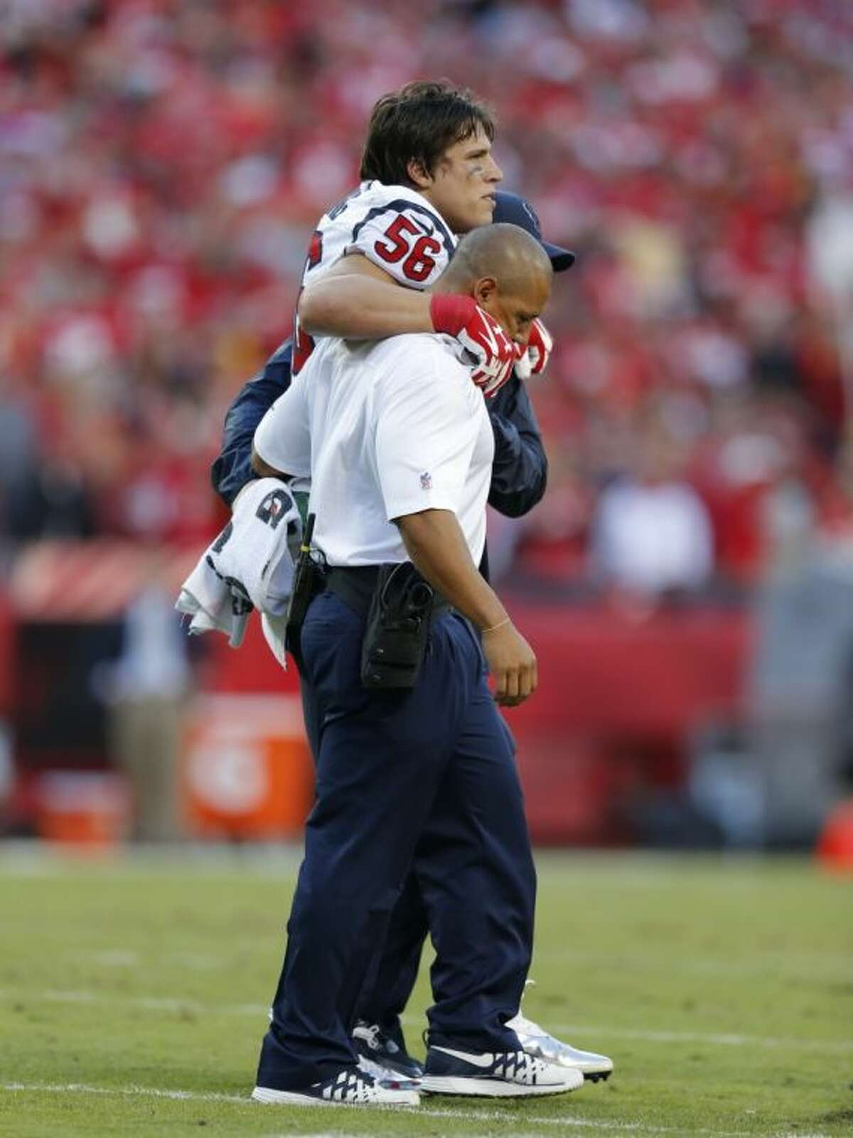 Texans linebacker Brian Cushing leaves the field with a knee injury Sunday.