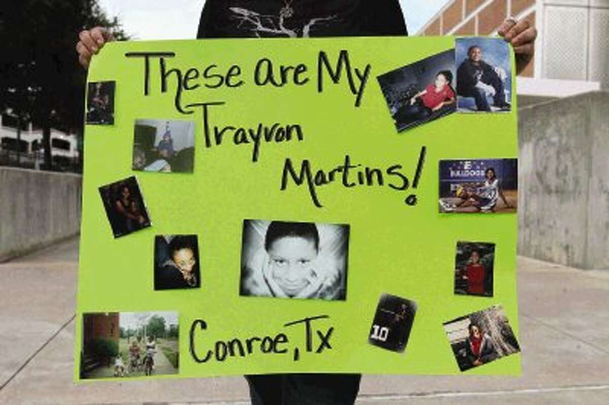 Misty Price holds up a sign showing her family members during a protest of the acquittal of George Zimmerman at Heritage Place Park in Conroe Wednesday. Protests have been held across the country after Zimmerman was found not guilty in the shooting death of unarmed teenager Trayvon Martin Saturday.