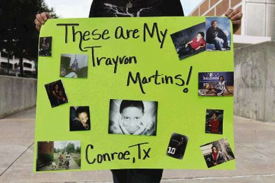 Misty Price holds up a sign showing her family members during a protest of the acquittal of George Zimmerman at Heritage Place Park in Conroe Wednesday. Protests have been held across the country after Zimmerman was found not guilty in the shooting death of unarmed teenager Trayvon Martin Saturday. Photo: Staff Photo By Jason Fochtman / Conroe Courier