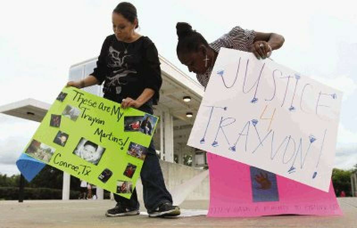 Misty Price and Kathalynn Abner switch signs during a protest of the acquittal of George Zimmerman at Heritage Place Park in Conroe Wednesday. Protests have been held across the country after Zimmerman was found not guilty in the shooting death of unarmed teenager Trayvon Martin Saturday.