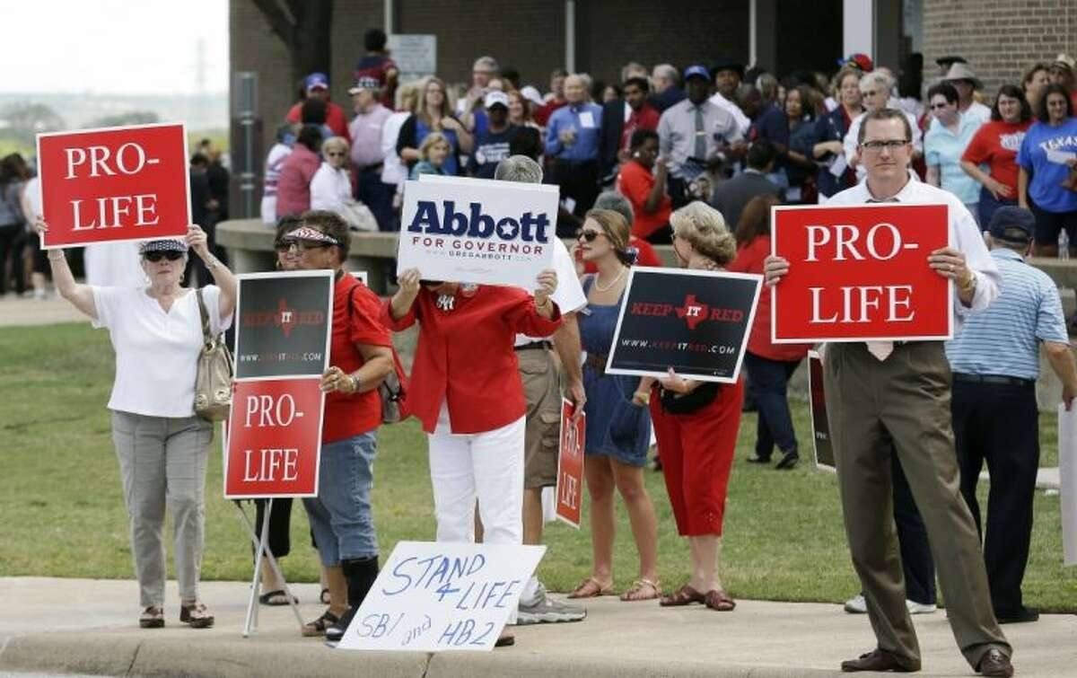 People hold signs protesting against State Sen. Wendy Davis as her supporters line up in the background outside the venue hosting a rally Thursday, Oct. 3, 2013, in Haltom City, Texas. Davis was expected to formally announce her campaign for governor Thursday, becoming the first Democrat to make an official bid for a statewide office.