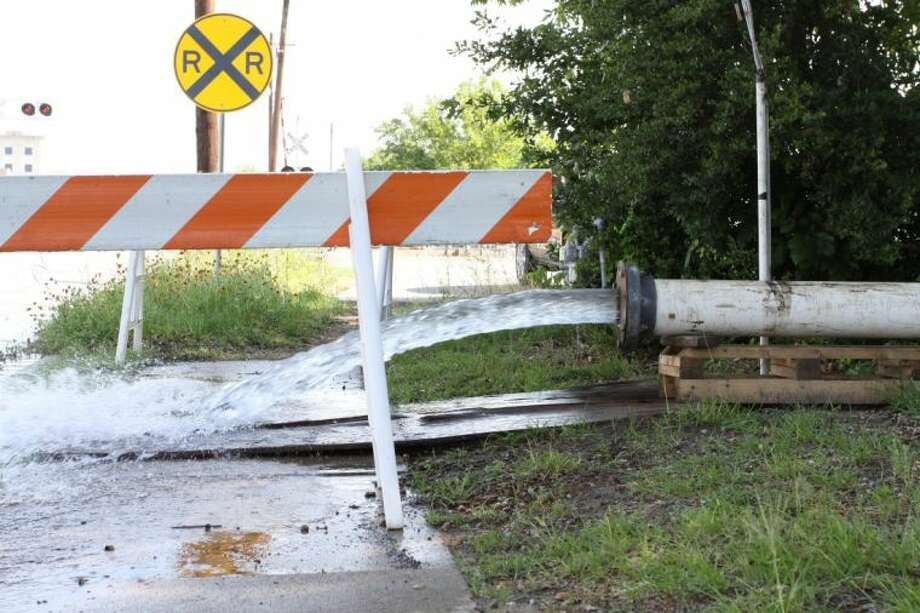 Water pours onto Frazier Street Thursday morning while city crews test a recent rehabilitated water well.