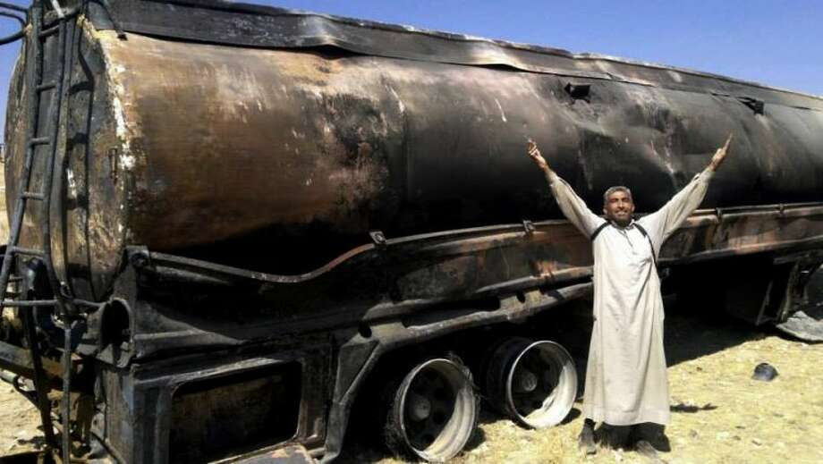 In this citizen journalism image provided by The Committee of Jabal al-Zawiyah, Jisr el-Sheghour, Maarat al-Naaman, Idlib, which has been authenticated based on its contents and other AP reporting, a Syrian man celebrates in front of a damaged government oil truck in Idlib province, Syria, Wednesday.
