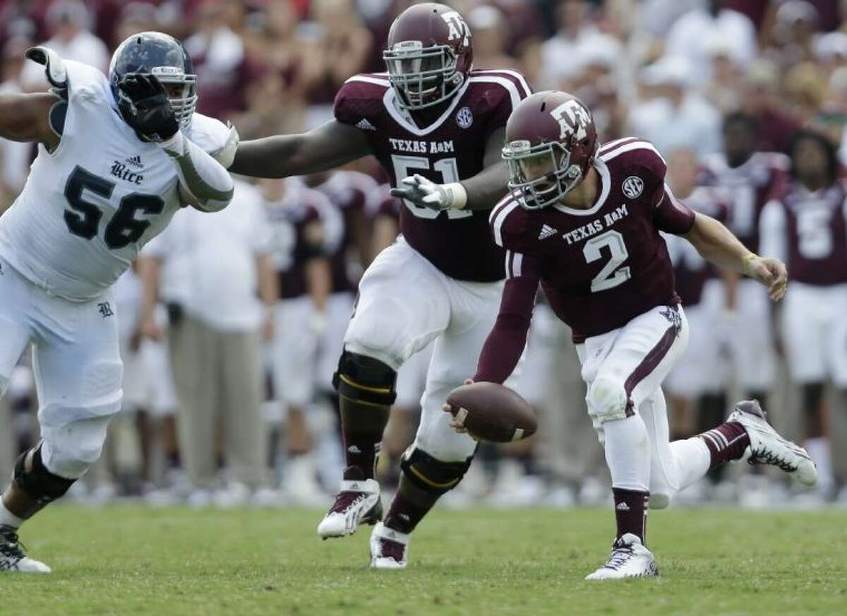Texas A&M's Johnny Manziel is pressured by Rice's Christian Covington. The Aggies whipped Rice 52-31.