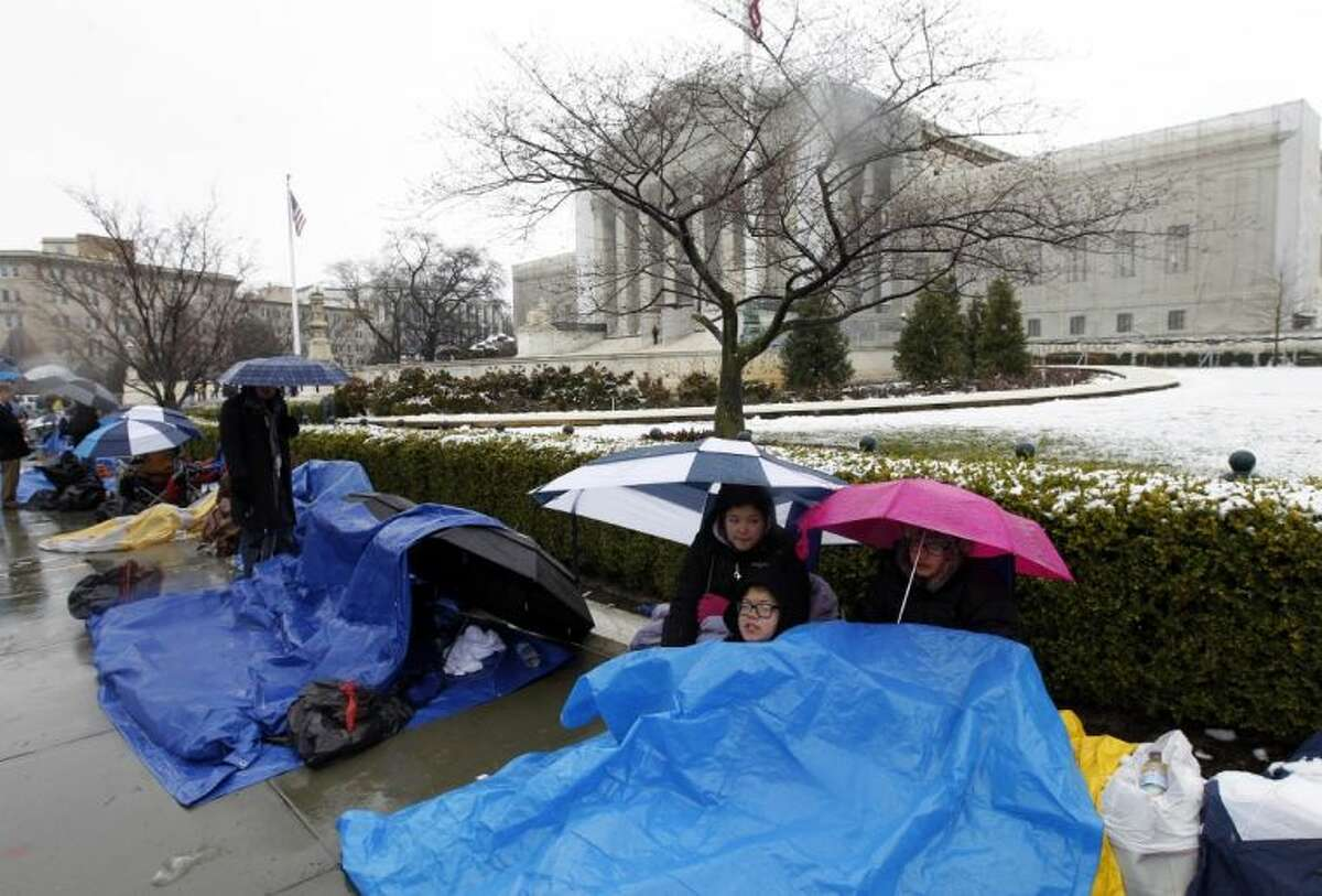 Taylor, Talla and Vincent Carter cover themselves from the snow as they wait in line outside of the Supreme Court in Washington, Monday March, 25, 2013, to watch Tuesday's same-sex marriage hearing before the Supreme Court.
