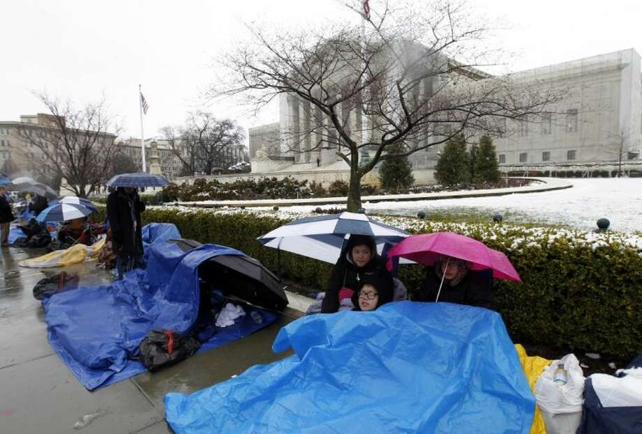 Taylor, Talla and Vincent Carter cover themselves from the snow as they wait in line outside of the Supreme Court in Washington, Monday March, 25, 2013, to watch Tuesday's same-sex marriage hearing before the Supreme Court. Photo: Jose Luis Magana