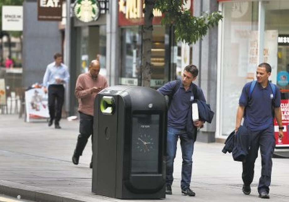 A man uses a trash bin in central London, Monday, Aug. 12, 2013. Officials say that an advertising firm must immediately stop using its network of high-tech trash cans, like this one, to track people walking through London's financial district. The City of London Corporation says it has demanded Renew pull the plug on the program, which measures the Wi-Fi signals emitted by smartphones to follow commuters as they pass the garbage cans.