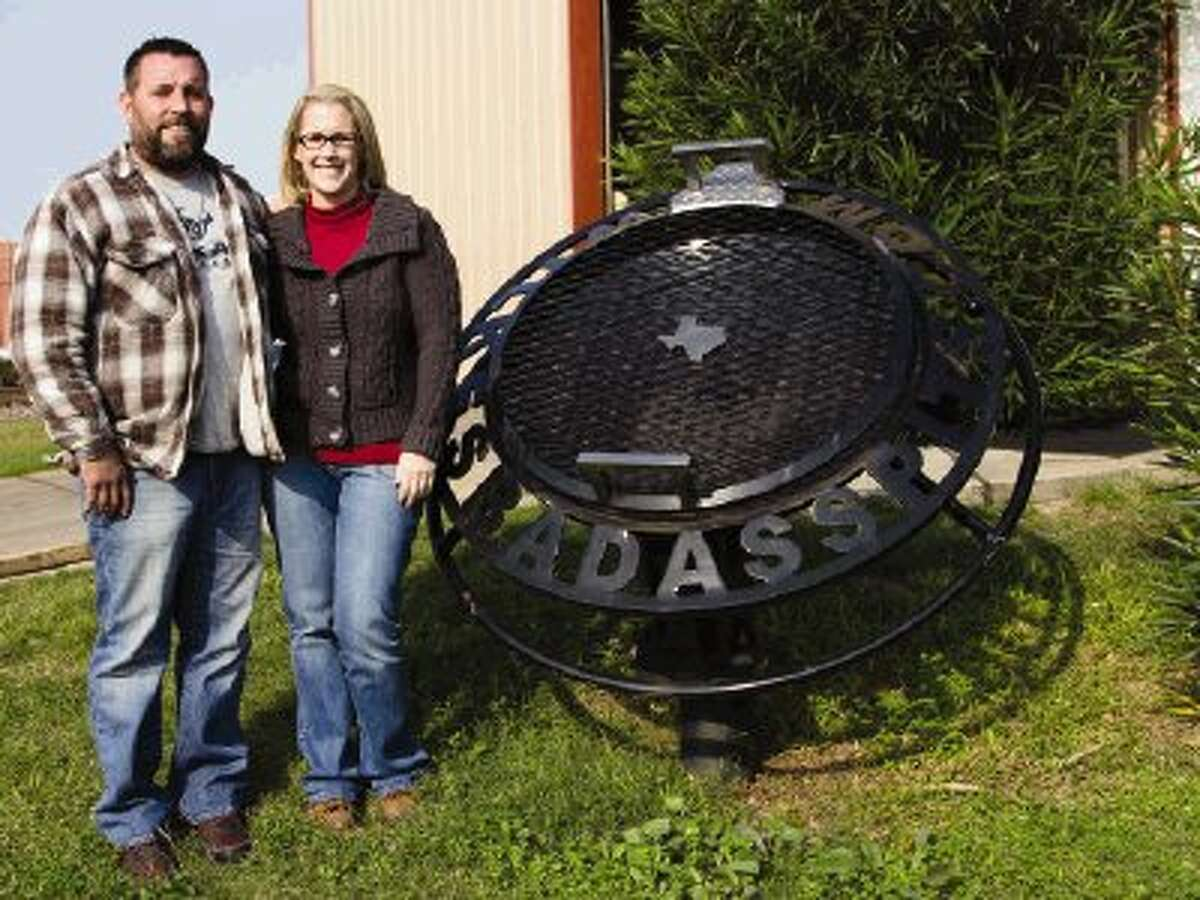 Brian and Angee Wilke, owners of Wilke's Badass Pits, stand outside of their shop in Conroe on Thursday. The company builds custom fire pits, smokers and grills in the Conroe and nearby areas.