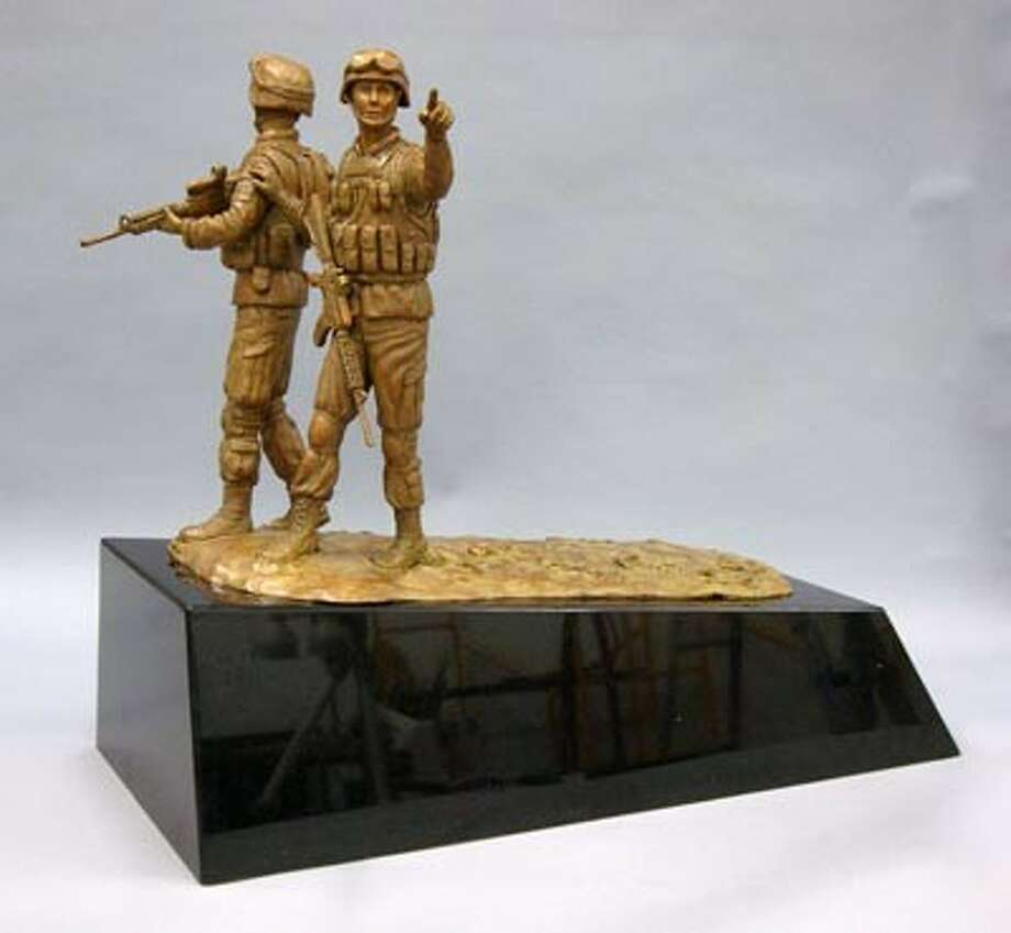Organizers with The Way Home project presented this 2-foot-tall replica of the proposed veterans memorial to Anadarko Petroleum in honor of the company's $25,000 donation toward the project. The proposed memorial, which has languished for several years, is once again gaining traction following donations. The proposed sculpture depicts two local veterans killed in action and 2,000 tiles with the names and titles of military men and women, and will be built at Town Green Park in The Woodlands.