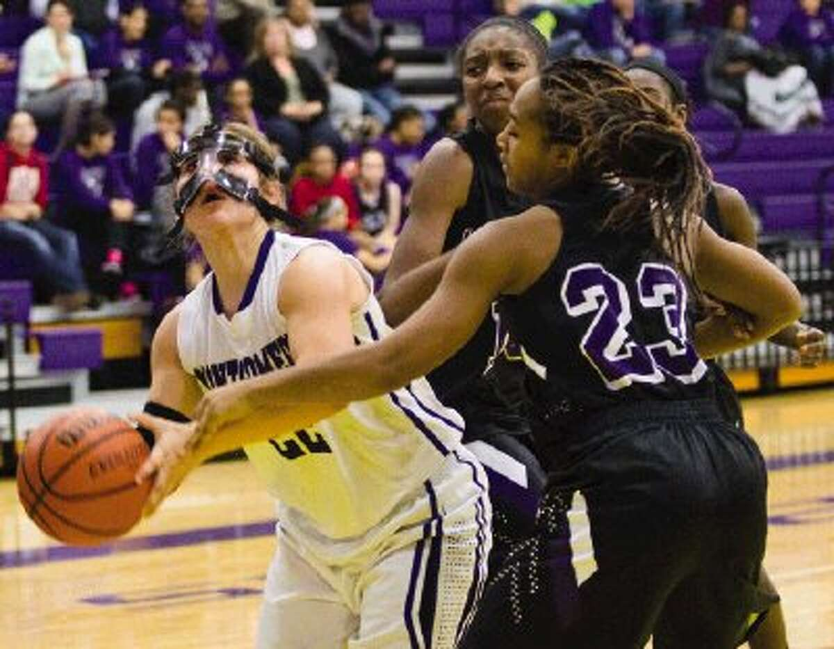 Montgomery's Marissa Garcia scores a basket as Willis' Kindallyn Reece and Brittany Johnson (23) defend during a District 18-4A game on Tuesday at Montgomery High School. To view or purchase this photo and others like it, visit HCNpics.com.