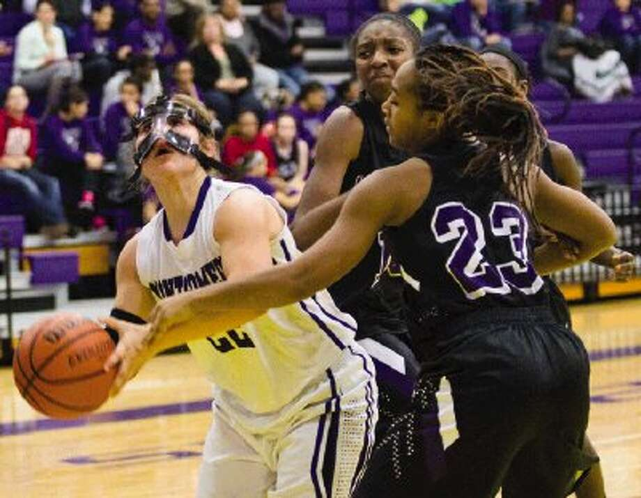 Montgomery's Marissa Garcia scores a basket as Willis' Kindallyn Reece and Brittany Johnson (23) defend during a District 18-4A game on Tuesday at Montgomery High School. To view or purchase this photo and others like it, visit HCNpics.com. Photo: Staff Photo By Ana Ramirez / The Conroe Courier/ The Woodland