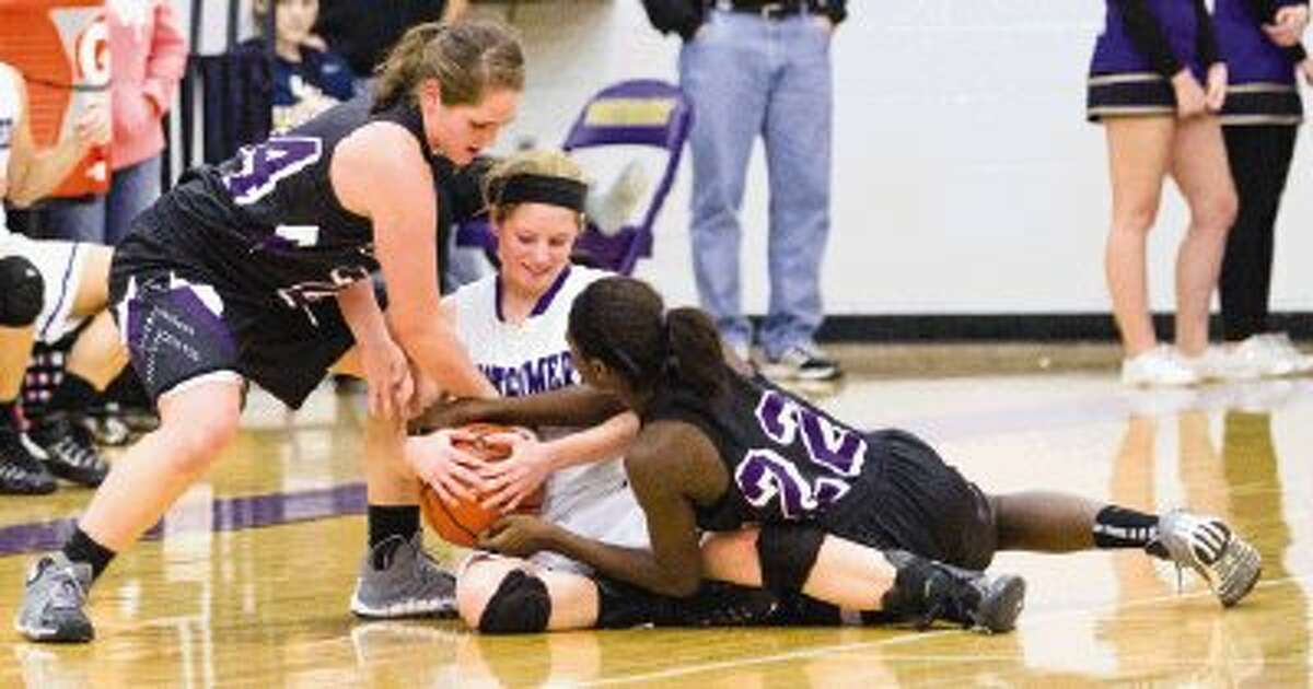 Montgomery's Macie Hance holds on to the ball as Willis' Calli Gray and Deseanna Murphy (22) try to take it away during a District 18-4A game on Tuesday at Montgomery High School. To view or purchase this photo and others like it, visit HCNpics.com.