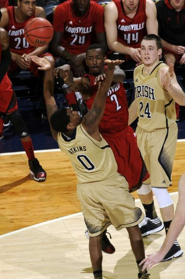 Louisville guard Russ Smith, middle, is trapped as he passes against Notre Dame's Eric Atkins, left, and Pat Connaughton. The Irish won 104-101 in five overtimes, the longest regular-season game in Big East history. Photo: Joe Raymond