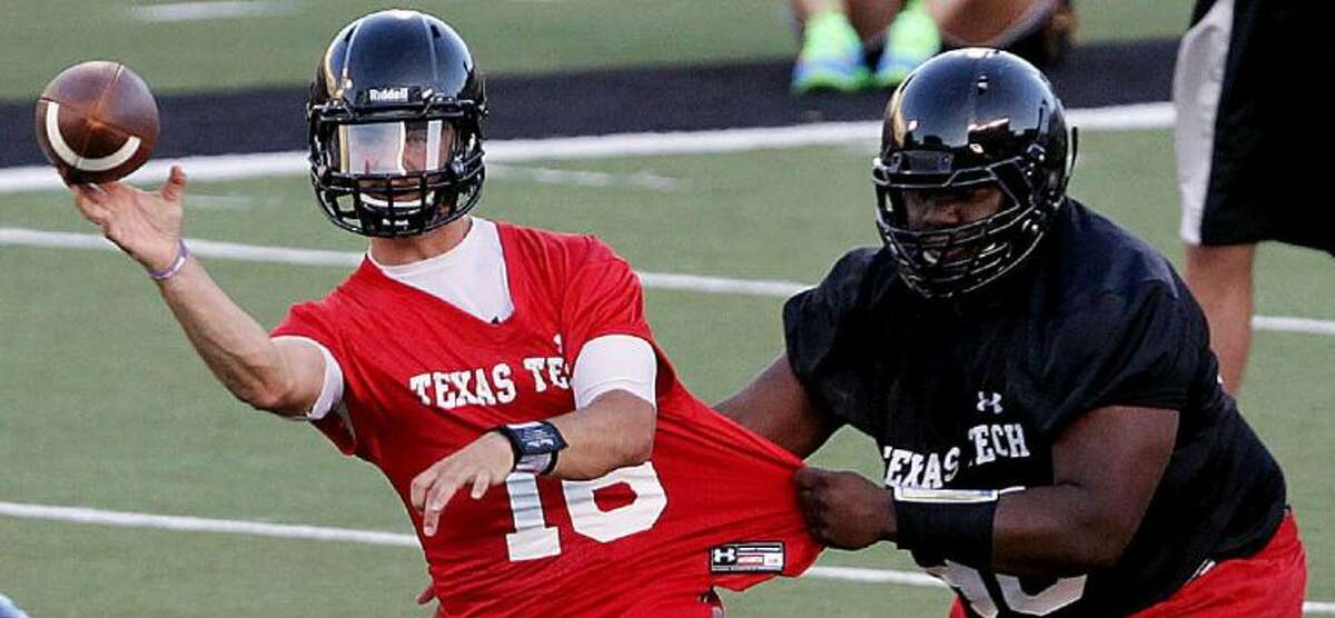 Texas Tech quarterback Michael Brewer throws a pass under pressure from Anthony Smith during practice on Aug. 3 in Lubbock.