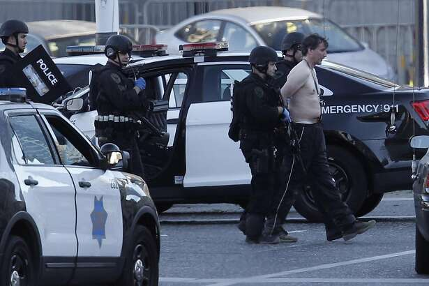 San Francisco Police officers responding reports of to a man with a gun arrest the suspect and lead him away in Civic Center Plaza in San Francisco, California on Sat. Sept. 24, 2016.