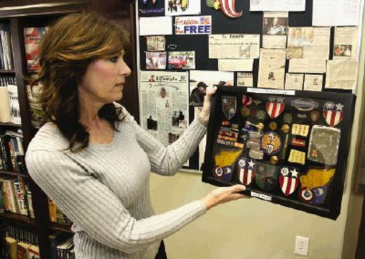 Pamela Miller looks over a display of some of the military awards, medals and campaign ribbons awarded to her father Clyde Miller, a member of the famous World War II fighting force, Merrill's Marauders.