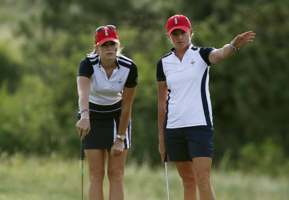 The Woodlands High School graduate Stacy Lewis, right, and Paula Creamer look over a birdie putt on the first hole during foursomes matches at the Solheim Cup on Saturday in Parker, Colo.