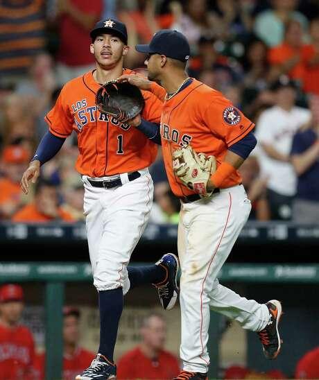 Shortstop Carlos Correa, left, celebrates a defensive gem with Yulieski Gurriel on Saturday night. Photo: Karen Warren, Staff Photographer / 2016 Houston Chronicle