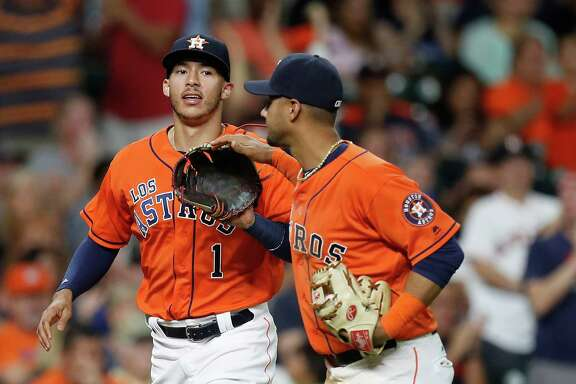 Astros shortstop Carlos Correa, left, celebrates a defensive gem with teammate Yulieski Gurriel during the sixth inning Saturday night at Minute Maid Park.