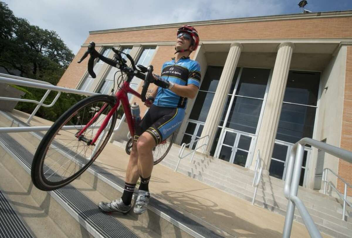 Jose Luis Bermudez, dean of the College of Liberal Arts at Texas A&M, carries his bike down the steps of the building where he works before heading home for the day, May 16, 2013.