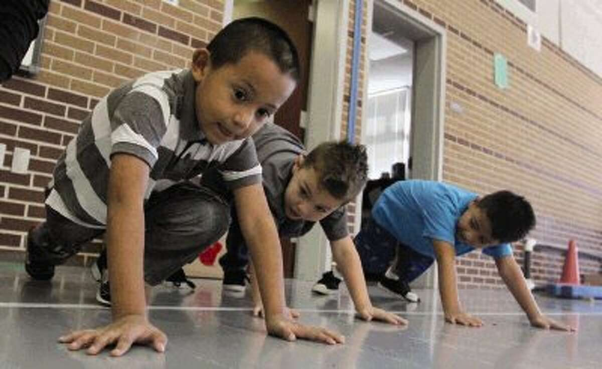 Students do push-ups after getting tagged as part of a game during a physical education class at Anderson Elementary in Conroe Thursday.