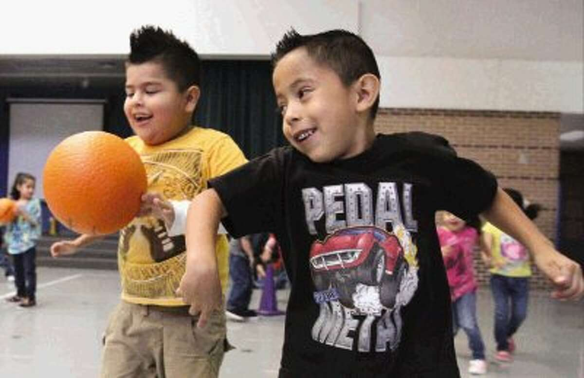 Adrian Rendon knocks the ball out of the hands of Nava Yahir during a physical education class at Anderson Elementary in Conroe Thursday.