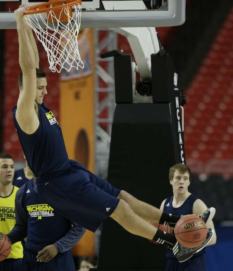 Michigan's Mitch McGary hangs from the rim during the Wolverines' Final Four practice. Michigan faces Syracuse tonight. Photo: John Bazemore