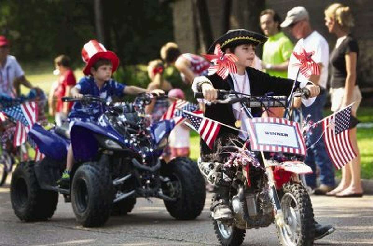 A young boy, dressed in colonial period costume, rides atop a decorated dirt bike during the Walden Property Owners Association's annual Independence Day Parade held Thursday morning in Walden. To view or order this photo and others like it, visit HCNPics.com.