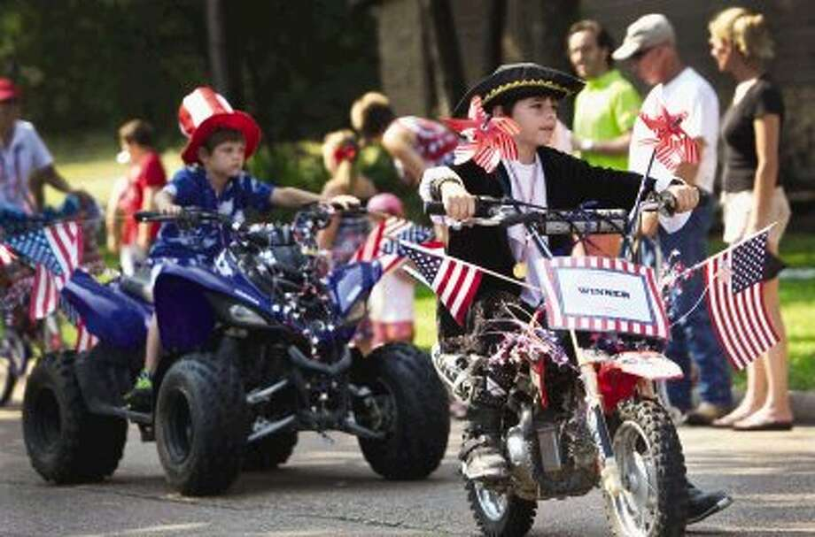 A young boy, dressed in colonial period costume, rides atop a decorated dirt bike during the Walden Property Owners Association's annual Independence Day Parade held Thursday morning in Walden. To view or order this photo and others like it, visit HCNPics.com. Photo: Staff Photo By Eric Swist
