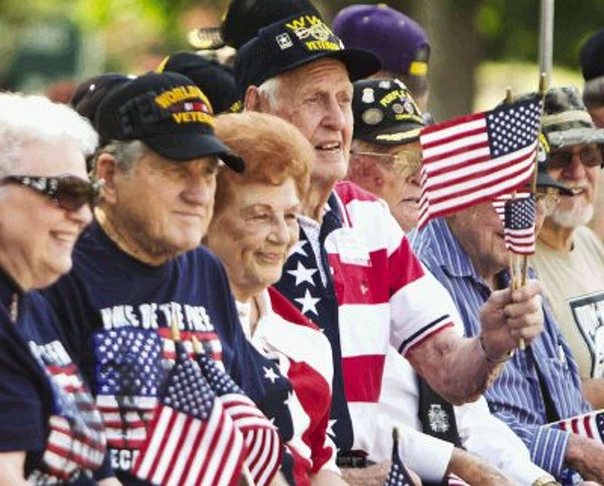 Veterans wave and hold American flags as they ride in a parade float during the Walden Property Owners Association's annual Independence Day Parade held Thursday morning in Walden.