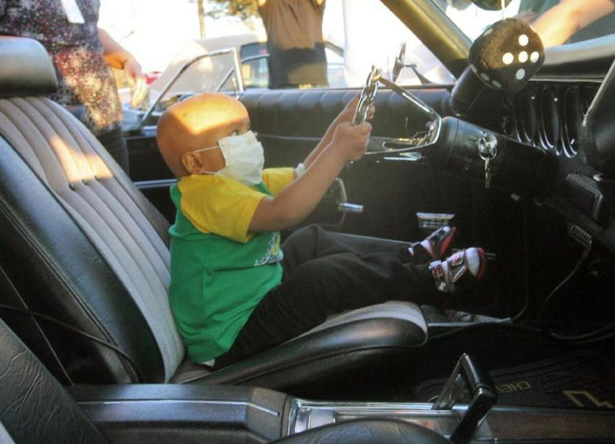 In this Feb. 5, 2013 photo, Fernando Cruz, 5, pretends to drive a custom classic car as part of a Make a Wish Foundation wish at the Edinburg Children's Hospital in Edinburg, Texas.